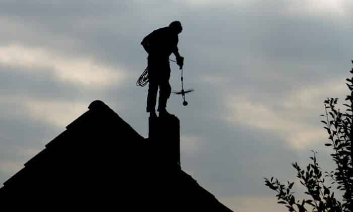 A chimney sweep stands above a chimney