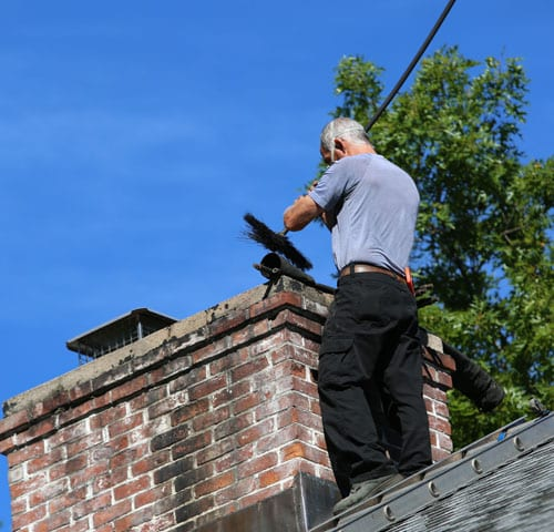 Technician Performing a Chimney Sweep