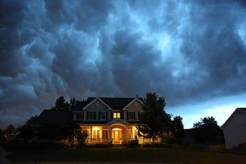 An upscale home sits under dark storm clouds.